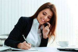 Young happy businesswoman talking on the phone and writing notes in office